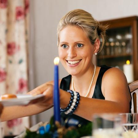 comida de navidad: Mujer en una cena de Navidad entregando una placa con una salchicha Foto de archivo