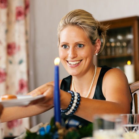christmas dish: Woman at a Christmas dinner handing over a plate with a sausage