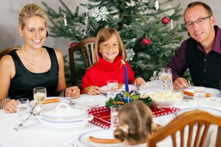 christmas dinner: Family eating a traditional Christmas Dinner in front of the Christmas tree Stock Photo