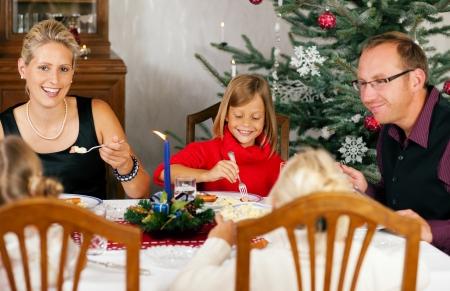 sacra famiglia: Famiglia a mangiare una cena tradizionale di Natale di fronte l'albero di Natale Archivio Fotografico