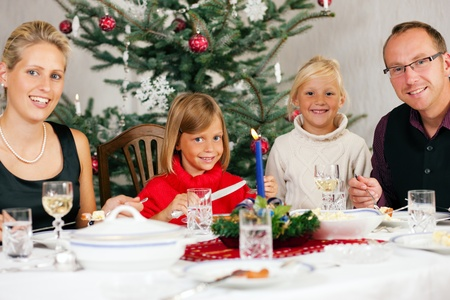 traditional christmas dinner: Family eating a traditional Christmas Dinner in front of the Christmas tree Stock Photo