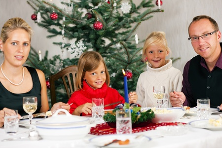 Family eating a traditional Christmas Dinner in front of the Christmas tree photo