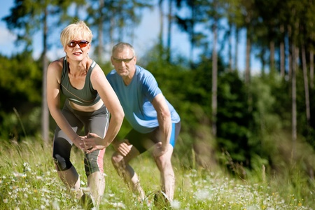 Mature or senior couple in jogging gear doing sport and physical exercise outdoors photo