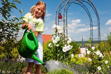 ewer: Happy child watering flowers in the garden  Stock Photo