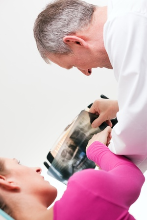 roentgenogram: Dentist explaining the details of a x-ray picture to his patient Stock Photo