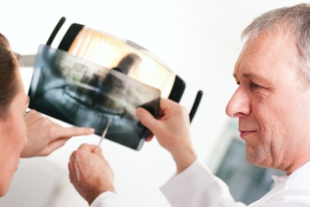 Dentist explaining the details of a x-ray picture to his patient photo