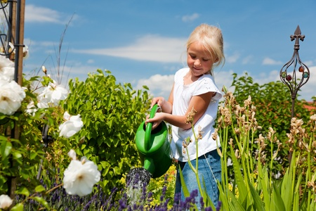 home garden: Happy child watering flowers in the garden  Stock Photo