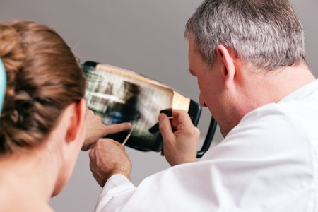 Dentist explaining the details of a x-ray picture to his patient Stock Photo - 10257359