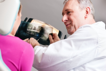 Dentist explaining the details of a x-ray picture to his patient, focus on eyes of doctor  Stock Photo