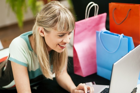 emphasized: Woman lying in her home living room on floor shopping or doing banking transactions online in the Internet, emphasized by shopping bags in the background