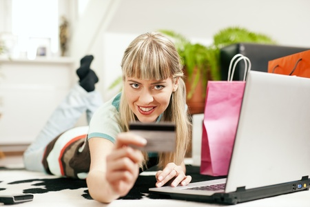 emphasized: Woman lying in her home living room on floor shopping or doing banking transactions online in the Internet, emphasized by shopping bags in the background and her holding a credit card