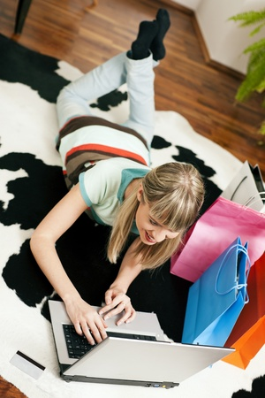 emphasized: Woman lying in her home living room on floor shopping or doing banking transactions online in the Internet, emphasized by shopping bags in the background and a credit card on the floor