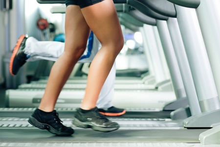 Woman and man in gym - only legs to be seen - exercising running on the treadmill to gain more fitness; motion blur in limbs for dynamic photo