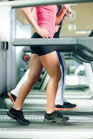 Woman and man in gym - only body to be seen - exercising running on the treadmill to gain more fitness; motion blur in limbs for dynamic photo