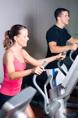 cardiovascular exercising: People - man and woman - exercising in a gym on an elliptical trainer for more fitness