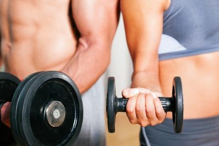 hombres haciendo ejercicio: Pareja ejercicio con pesas en un gimnasio, centrarse en los pesos, sólo de torso de hombre y mujer a verse