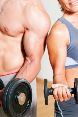 man lifting weights: Couple exercising with dumbbells in a gym, focus on the weights, only torso of man and woman to be seen Stock Photo