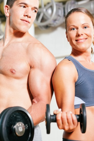 Couple exercising with dumbbells in a gym, focus on eyes of man and woman photo
