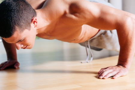 masculine: Strong, handsome man doing push-ups in a gym as bodybuilding exercise, training his muscles