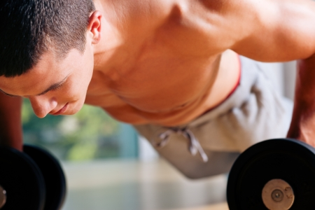push ups: Strong, handsome man doing push-ups in a gym as bodybuilding exercise, training his muscles