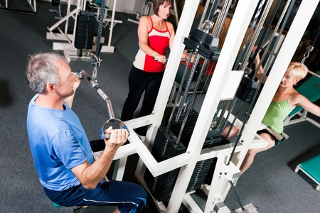 Senior people in a gym exercising on a pulldown machine   photo