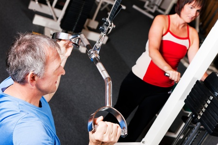 Senior people in a gym exercising on a pulldown machine Stock Photo - 10258827