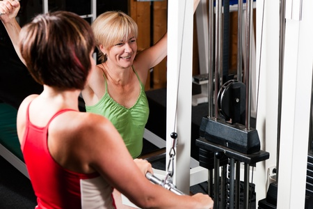 Senior people in a gym exercising on a pulldown machine Stock Photo - 10257428