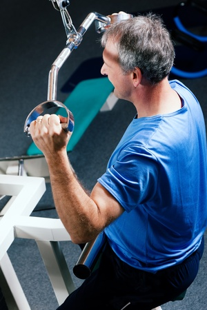 Senior man in the gym lifting weights on a lat pull machine, exercising Stock Photo - 10258841