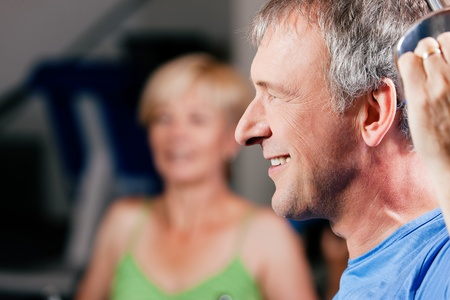 Senior couple -  man and woman - in the gym lifting weights on a lat pull machine, exercising Stock Photo - 10258842