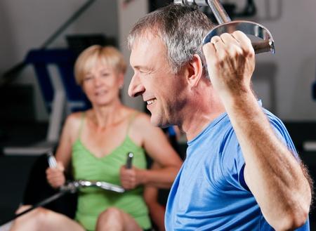lifting weights: Matrimonios de edad - hombre y mujer - en el gimnasio levantando pesas en una m�quina de tirar lat, el ejercicio de