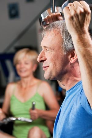 men exercising: Senior pareja - hombre y mujer - en el gimnasio levantando pesas en una m�quina de tracci�n de latitud, en el ejercicio