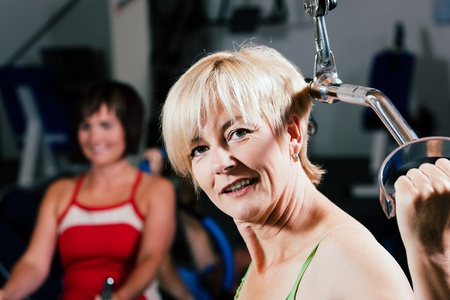 Senior woman in the gym lifting weights on a lat pull machine, exercising Stock Photo - 10258824