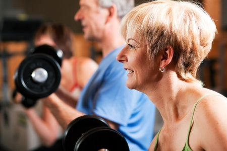 Senior people in a gym exercising with weights    Stock Photo