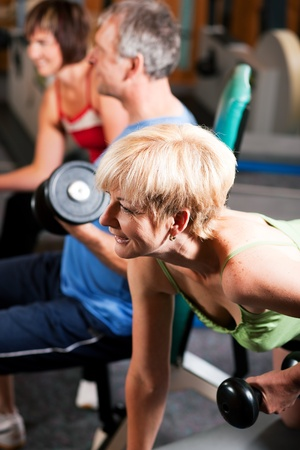 Senior people in a gym exercising with weights Stock Photo - 10257316