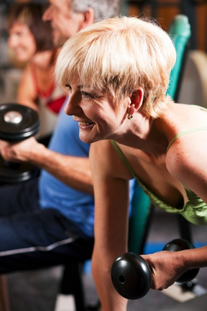 Senior people in a gym exercising with weights    Stock Photo - 10258813