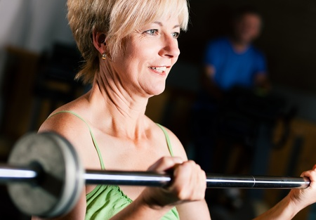 Senior woman in a gym exercising with barbell