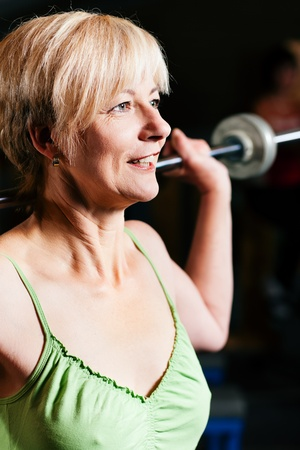 barbell: Senior woman in a gym exercising with barbell