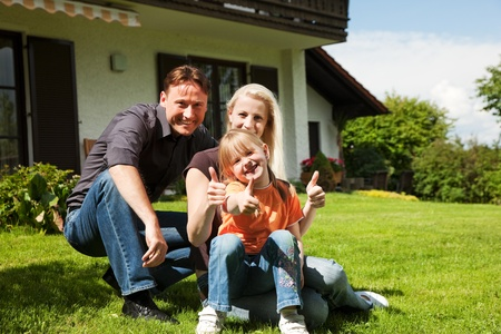 single family house: Young family sitting in the sun on the lawn in front of their new home - a single house