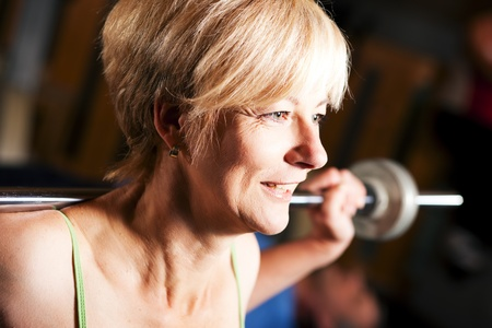 Senior woman in a gym exercising with barbell   photo