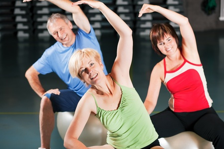 senior exercising: Senior people in a gym exercising with fitness ball    Stock Photo