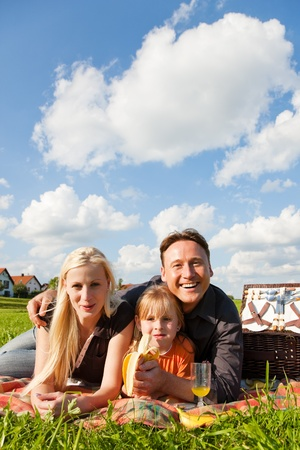 family picnic: Family - father, mother and daughter child - having a picnic on a green meadow on a beautiful and bright summer day
