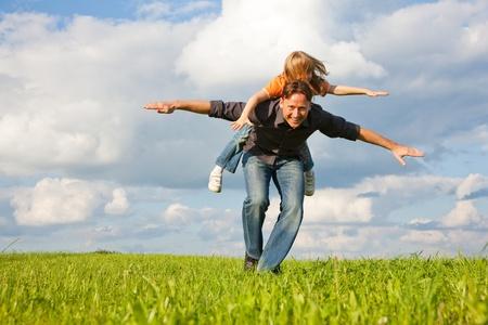 háton: Atya és a fiát - a lánya - játszik együtt a réten, ő vitte háton Stock fotó