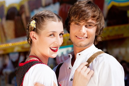 dult: Young and beautiful couple in traditional Bavarian Tracht - Dirndl and Lederhosen - embracing each other on a fair like a Dult or the Oktoberfest; both are standing in front of a typical booth