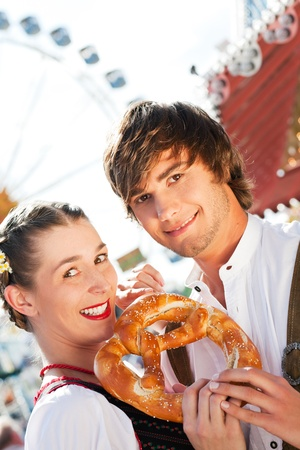wiesn: Young and beautiful couple in traditional Bavarian Tracht - Dirndl and Lederhosen - embracing each other on a fair like a Dult or the Oktoberfest eating a pretzel