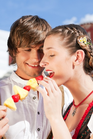 tracht: Young and beautiful couple in traditional Bavarian Tracht - Dirndl and Lederhosen - embracing each other on a fair like a Dult or the Oktoberfest eating traditional fruits