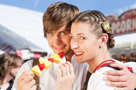 dult: Young and beautiful couple in traditional Bavarian Tracht - Dirndl and Lederhosen - embracing each other on a fair like a Dult or the Oktoberfest eating traditional fruits