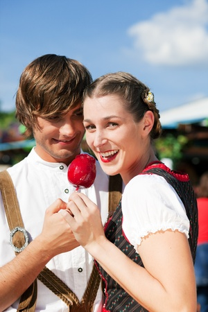 wiesn: Young and beautiful couple in traditional Bavarian Tracht - Dirndl and Lederhosen - embracing each other on a fair like a Dult or the Oktoberfest eating traditional sugar apple Stock Photo