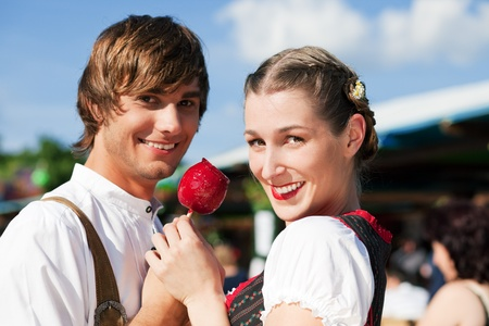 Young and beautiful couple in traditional Bavarian Tracht - Dirndl and Lederhosen - embracing each other on a fair like a Dult or the Oktoberfest eating traditional sugar apple photo