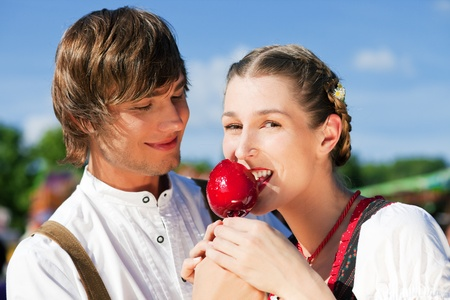 dult: Young and beautiful couple in traditional Bavarian Tracht - Dirndl and Lederhosen - embracing each other on a fair like a Dult or the Oktoberfest eating traditional sugar apple Stock Photo