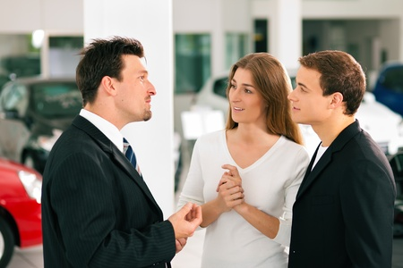 Sales situation in a car dealership, the dealer is talking to a young couple, there are cars standing in the background Stock Photo - 10260890